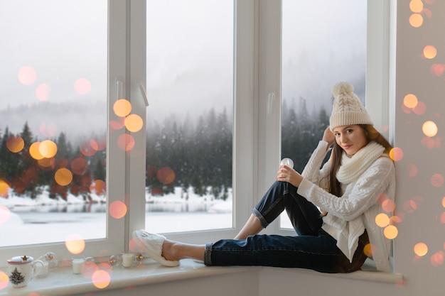 Jonge aantrekkelijke vrouw in stijlvolle witte gebreide trui, sjaal en muts om thuis te zitten op de vensterbank met kerstmis glas sneeuw bal aanwezig decoratie, winter boszicht, lichten bokeh houden Gratis Foto