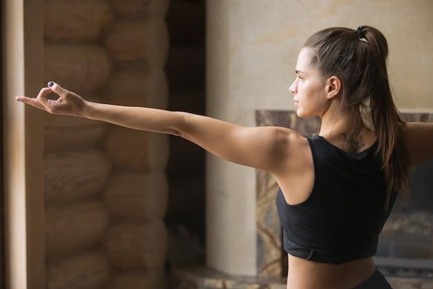 Jonge aantrekkelijke vrouw in warrior twee poseren, interieur backgr Gratis Foto