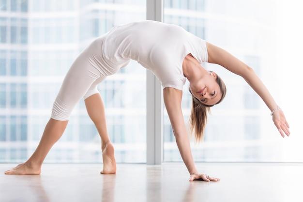 Jonge aantrekkelijke vrouw in yoga pose Gratis Foto
