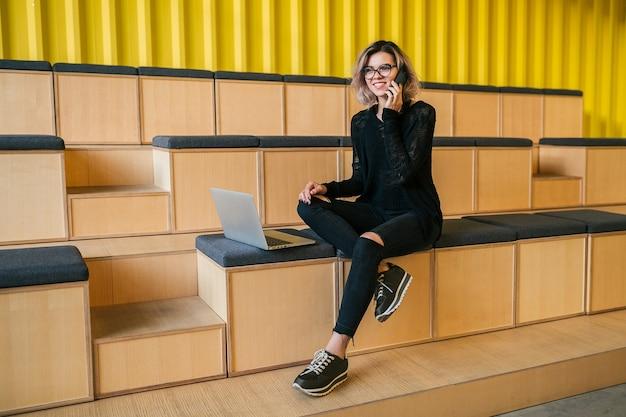 Jonge aantrekkelijke vrouw zitten in collegezaal, bezig met laptop, bril, moderne auditorium, student onderwijs online, freelancer, glimlachen, praten aan de telefoon Gratis Foto