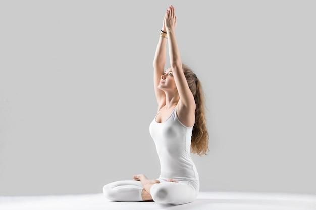 Jonge aantrekkelijke vrouw zitten in padmasana poseren, grijze studio ba Gratis Foto