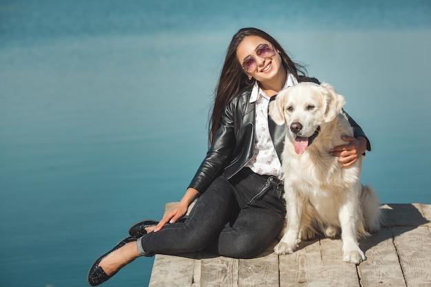 Jonge aantrekkelijke vrouw zitten op de pier met haar hond. beste vrienden buitenshuis Premium Foto