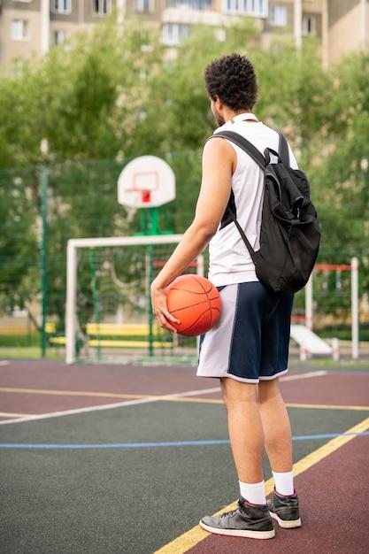 Jonge actieve mannelijke basketbalspeler met bal en rugzak die zich door witte lijn op speelplaats bevinden Premium Foto