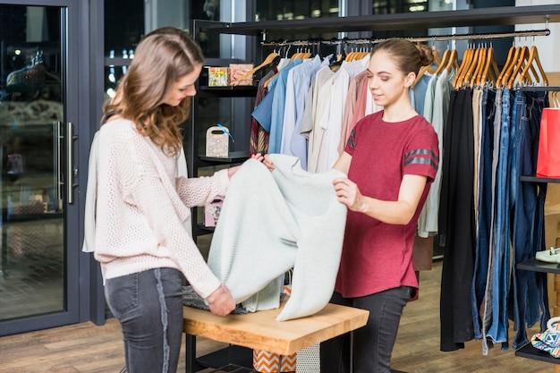 Jonge adviseur die kleren tonen aan de klant bij winkelcentrum Gratis Foto