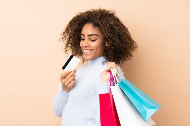 Jonge african american vrouw geïsoleerd op beige boodschappentassen houden en een creditcard Premium Foto