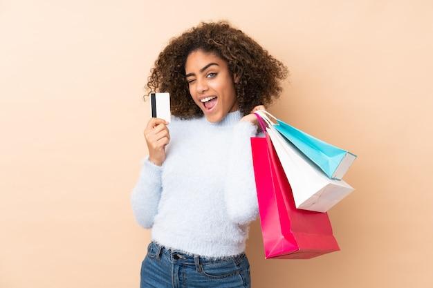 Jonge african american vrouw op beige muur boodschappentassen houden en een creditcard Premium Foto