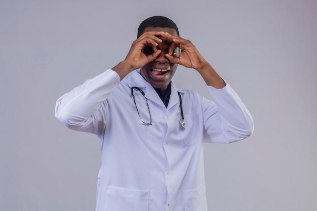 Jonge afrikaanse amerikaanse arts die witte jas met stethoscoop draagt die ok gebaar zoals verrekijker doet die door vingers tong uitsteekt kijken Gratis Foto