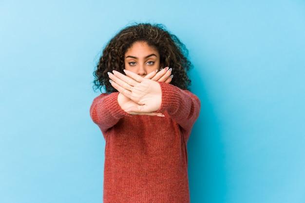 Jonge afrikaanse amerikaanse krullende haarvrouw die een ontkenningsgebaar doet Premium Foto