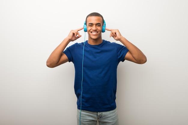 Jonge afrikaanse amerikaanse mens die op witte muur aan muziek met hoofdtelefoons luistert Premium Foto