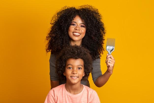 Jonge afrikaanse amerikaanse mensen die geïsoleerd haar kammen. vork voor het kammen van gekruld haar. gele muur. Premium Foto