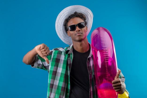 Jonge afrikaanse amerikaanse reizigersmens die in zomerhoed zwarte zonnebril dragen die opblaasbare ring houden ontevreden tonen duimen neer die zich over blauwe achtergrond bevinden Gratis Foto