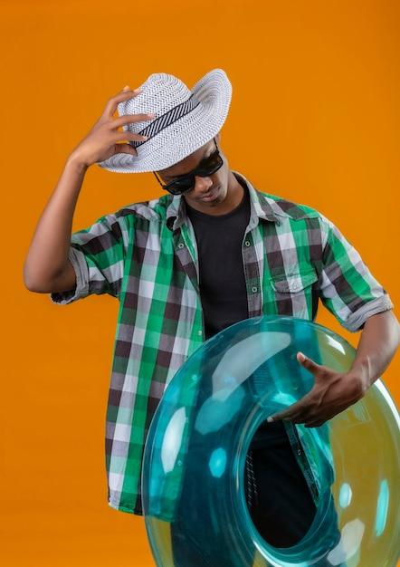 Jonge afrikaanse amerikaanse reizigersmens in de zomerhoed die zwarte zonnebril draagt die opblaasbare ring houdt die neerkijkt wat betreft zijn hoed die zich over oranje achtergrond bevindt Gratis Foto