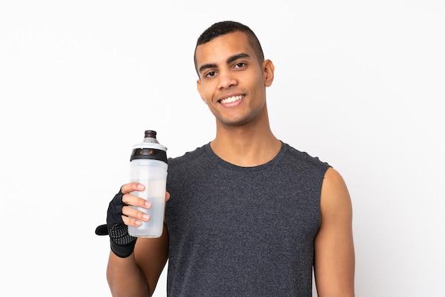 Jonge afrikaanse amerikaanse sportmens over geïsoleerde witte muur met de fles van het sportenwater Premium Foto