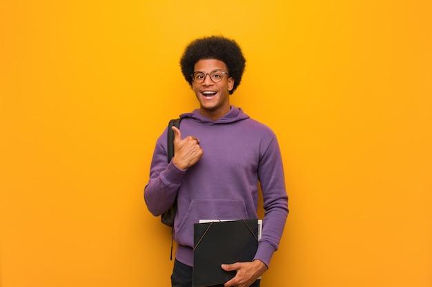 Jonge afrikaanse amerikaanse student man verrast, voelt zich succesvol en welvarend Premium Foto