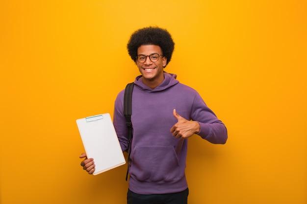 Jonge afrikaanse amerikaanse studentenmens die een klembord houdt glimlachend en duim opheffend Premium Foto