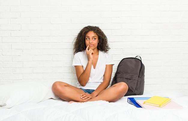 Jonge afrikaanse amerikaanse studentenvrouw op het bed die zijdelings met twijfelachtige en sceptische uitdrukking kijken. Premium Foto