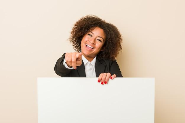 Jonge afrikaanse amerikaanse vrouw die een aanplakbiljet vrolijke glimlachen houden die naar voorzijde richten. Premium Foto