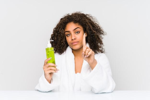 Jonge afrikaanse amerikaanse vrouw die een aloë vera houdt dat nummer één met vinger toont. Premium Foto