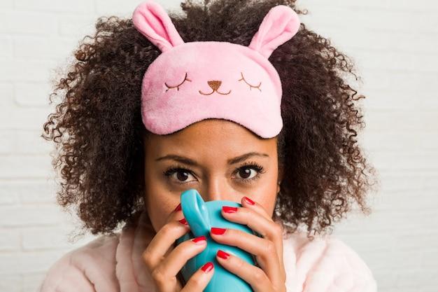 Jonge afrikaanse amerikaanse vrouw die een kop op het bed houdt Premium Foto