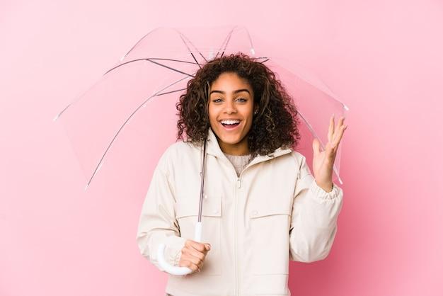Jonge afrikaanse amerikaanse vrouw die een paraplu houdt die een aangename verrassing ontvangt, opgewekt en handen opheft. Premium Foto
