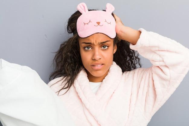 Jonge afrikaanse amerikaanse vrouw die pyjama's en een slaapmasker draagt dat een hoofdkussen houdt dat wordt geschokt, heeft zij belangrijke vergadering herinnerd. Premium Foto