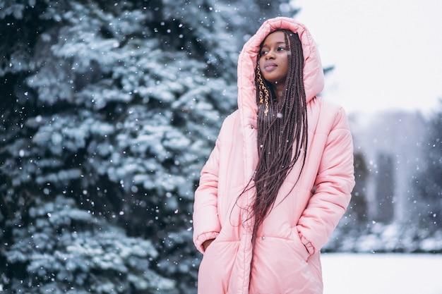Jonge afrikaanse amerikaanse vrouw in de winter buiten in park Gratis Foto