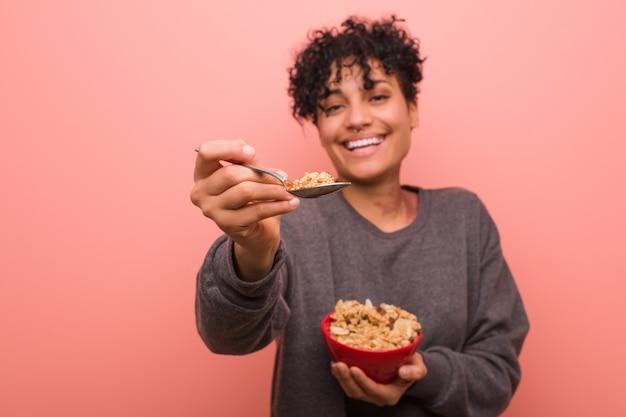 Jonge afrikaanse amerikaanse vrouw met een moedervlek die een graangewassenkom houdt Premium Foto