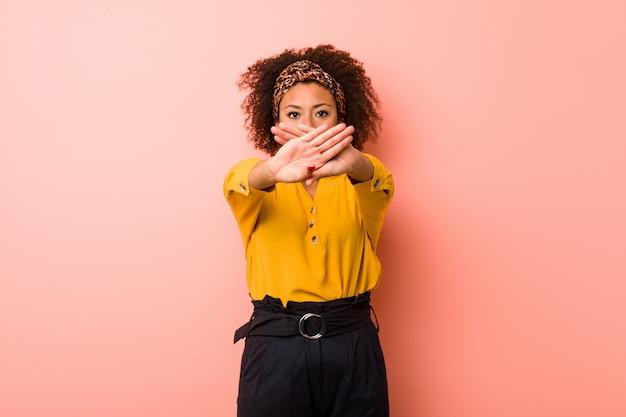 Jonge afrikaanse amerikaanse vrouw tegen een roze muur die een ontkenningsgebaar doet Premium Foto