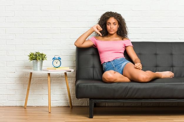 Jonge afrikaanse amerikaanse vrouwenzitting op de bank die een afkeergebaar tonen, duimen neer. meningsverschil concept. Premium Foto