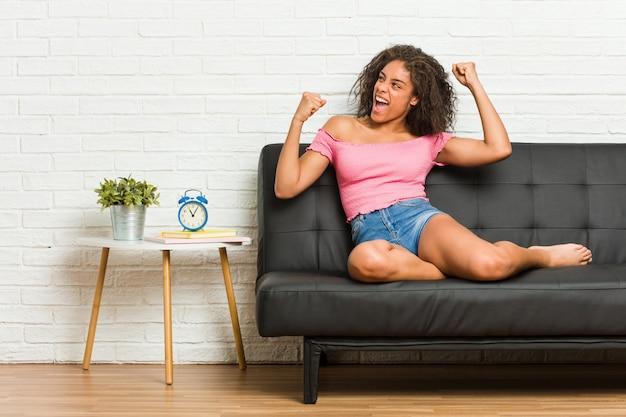 Jonge afrikaanse amerikaanse vrouwenzitting op de bank die vuist na een overwinning opheffen Premium Foto