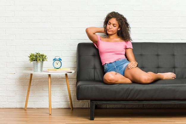 Jonge afrikaanse amerikaanse vrouwenzitting op de bank wat betreft achterhoofd, het denken en het maken van een keus. Premium Foto