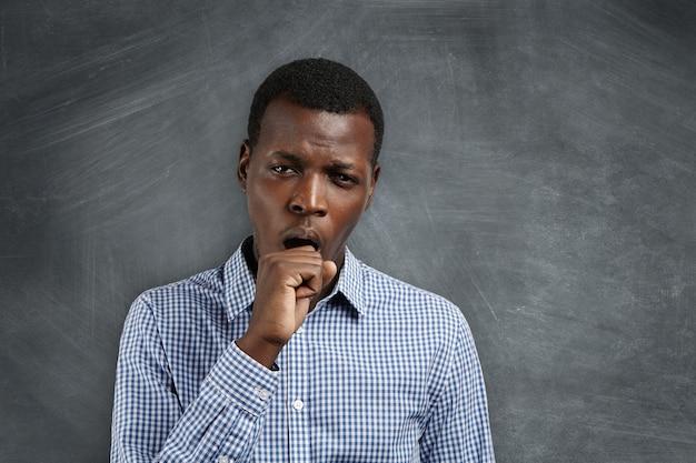 Jonge afrikaanse leraar die er moe en slaperig uitziet, geeuwt, zijn mond bedekt met, na een slapeloze nacht. zwarte student kijkt verveeld en ongeïnteresseerd tijdens wiskundelessen op de universiteit. Gratis Foto