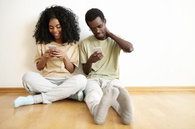Jonge afrikaanse man en vrouw met behulp van gratis wi-fi thuis, zittend op de houten vloer naast elkaar: vrouw berichten vrienden online via sociale netwerken Gratis Foto