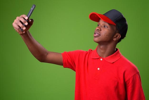 Jonge afrikaanse man tegen groene muur Premium Foto