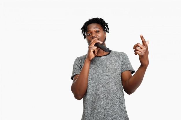 Jonge afrikaanse man zingen in microfoon op wit. Gratis Foto