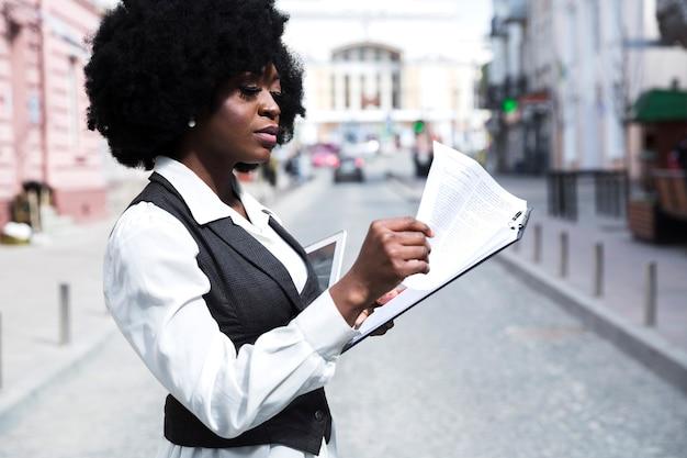 Jonge afrikaanse onderneemster die zich op weg bevindt die het document op klembord leest Gratis Foto