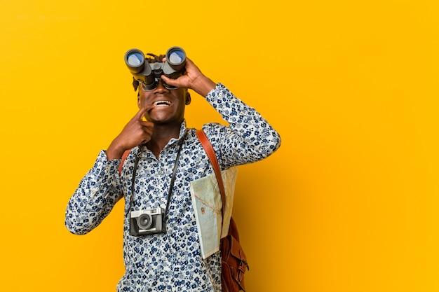 Jonge afrikaanse toeristenmens die houdend verrekijkers bevinden zich Premium Foto