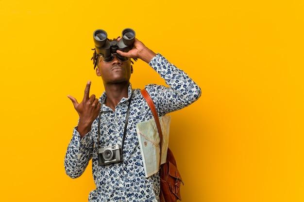 Jonge afrikaanse toeristenmens die zich tegen een geel bevindt die verrekijkers houdt Premium Foto