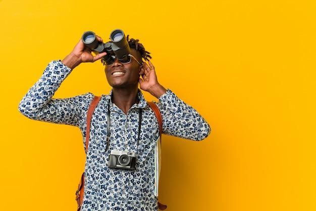 Jonge afrikaanse toeristenmens die zich tegen een gele muur bevindt die verrekijkers houdt Premium Foto