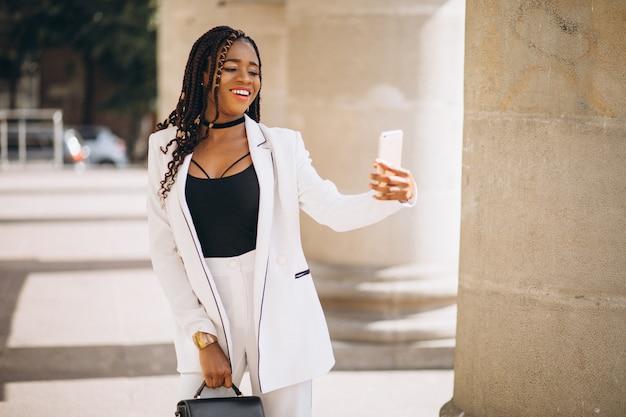 Jonge afrikaanse vrouw in wit pak met behulp van de telefoon Gratis Foto