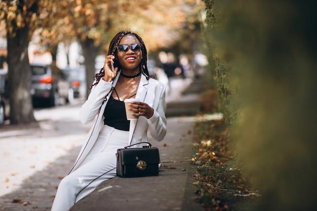 Jonge afrikaanse vrouw koffie drinken en het gebruik van de telefoon Gratis Foto