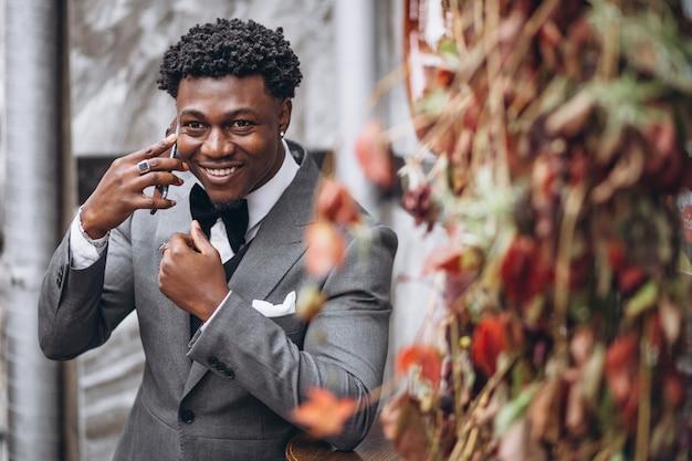 Jonge afrikaanse zakenman die telefoon met behulp van Gratis Foto