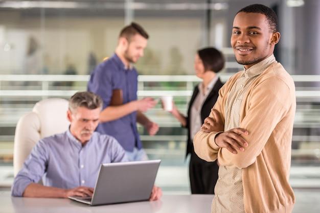 Jonge afrikaanse zakenman die zich met gekruiste handen bevindt. Premium Foto