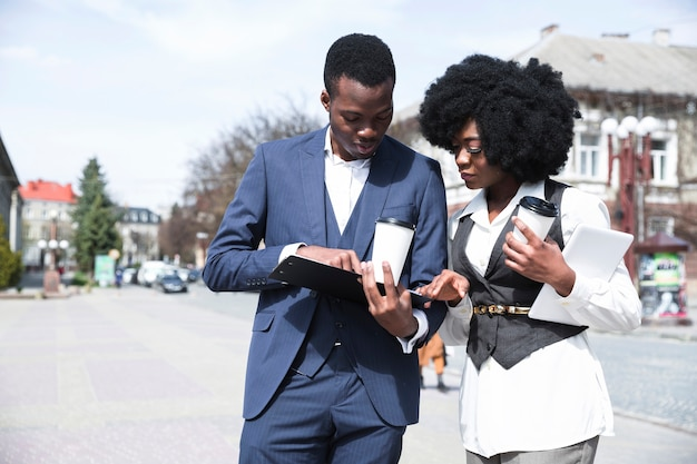 Jonge afrikaanse zakenman en onderneemster die in het klembord kijken Gratis Foto