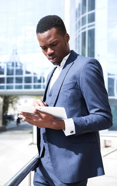 Jonge afrikaanse zakenman in blauw pak met behulp van digitale tablet in openlucht Gratis Foto