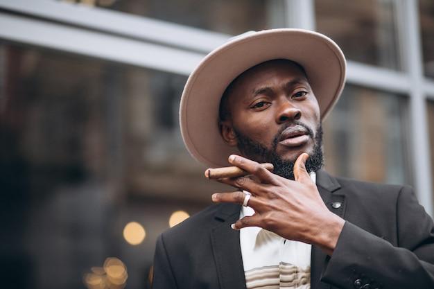 Jonge afrikaanse zakenman in stijlvolle pak rokende sigaret Gratis Foto