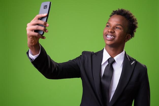 Jonge afrikaanse zakenman tegen groene muur Premium Foto