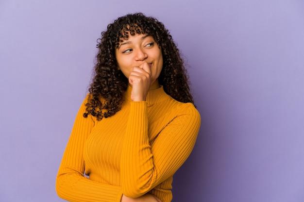 Jonge afro-amerikaanse afro vrouw geïsoleerd ontspannen denken aan iets kijken naar een kopie ruimte. Premium Foto