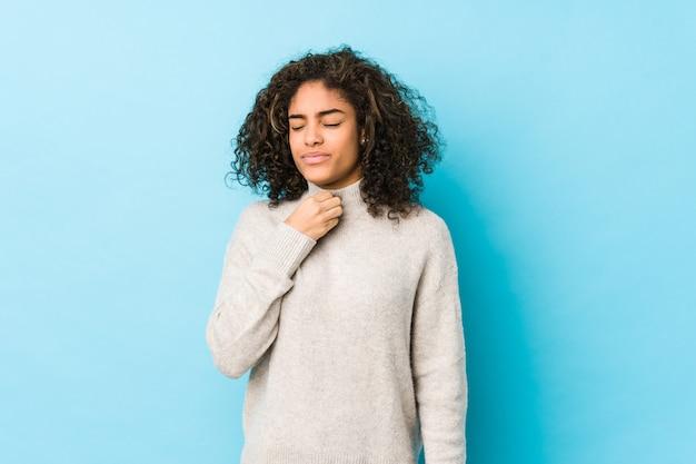 Jonge afro-amerikaanse krullende haarvrouw lijdt pijn in de keel door een virus of infectie. Premium Foto