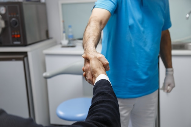 Jonge afro-amerikaanse man die hand van tandarts schudt die bezoek in medische kliniek heeft. Premium Foto